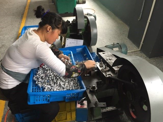 Stamping small metal parts… one at a time, by hand. They do a lot of work manually we would automate here. At $2.00 an hour for manufacturing wages, the cost is cheaper for them to do it manually.